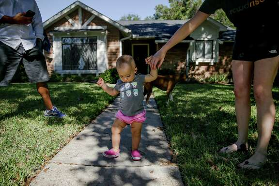 Amanda Reynado on Thursday helps her 15-month-old daughter, Finley, walk in front of their house on Wigton Drive in voting precinct 403. The neighborhood has the highest voter turnout in the city. Reynado and her husband, JJ, already voted early for the upcoming election.