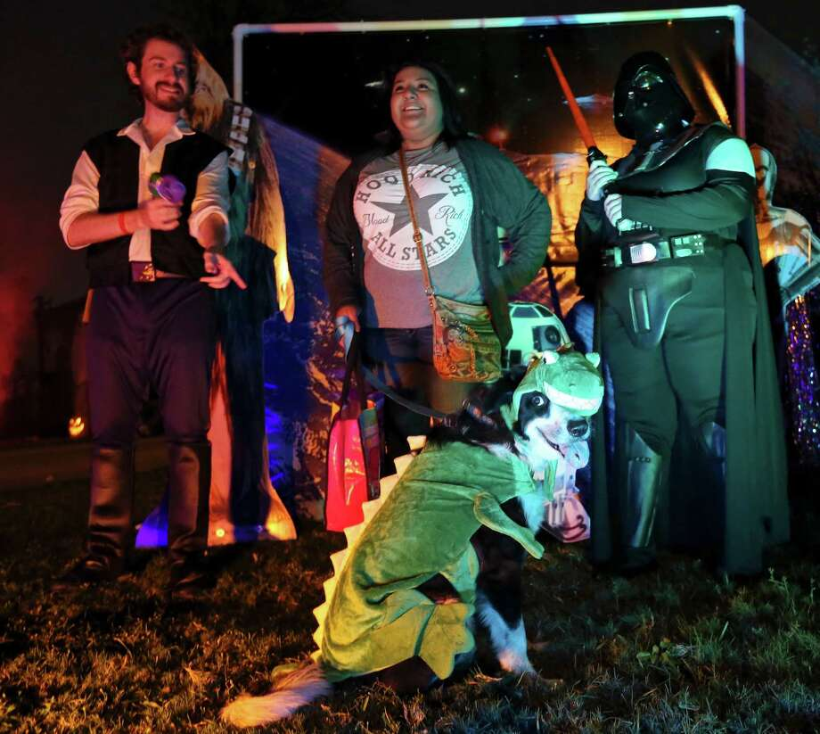 Isabella Ponce and her dog Gus pose for photos with Greg White as Han Solo (left) and Jackie Naehrig as Darth Vader Saturday Oct. 31, 2015 at Patricia Dorantes' Star Wars themed home. Photo: Edward A. Ornelas, Staff / San Antonio Express-News / © 2015 San Antonio Express-News