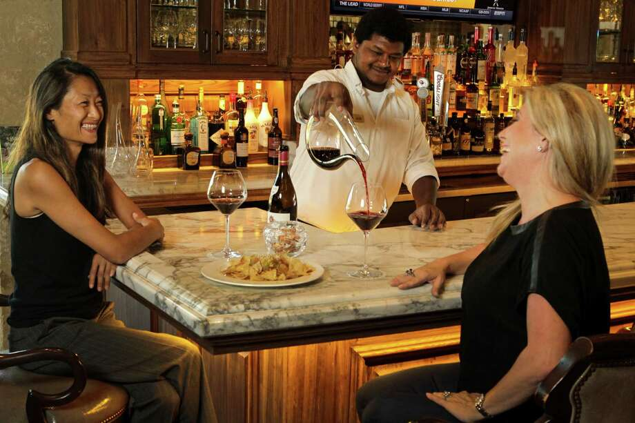 At Houston Oaks Country Club, Joshua Silsby serves members Cecilia Brown, left, and Angela Gutierrez. Photo: Melissa Phillip, Staff / © 2015 Houston Chronicle
