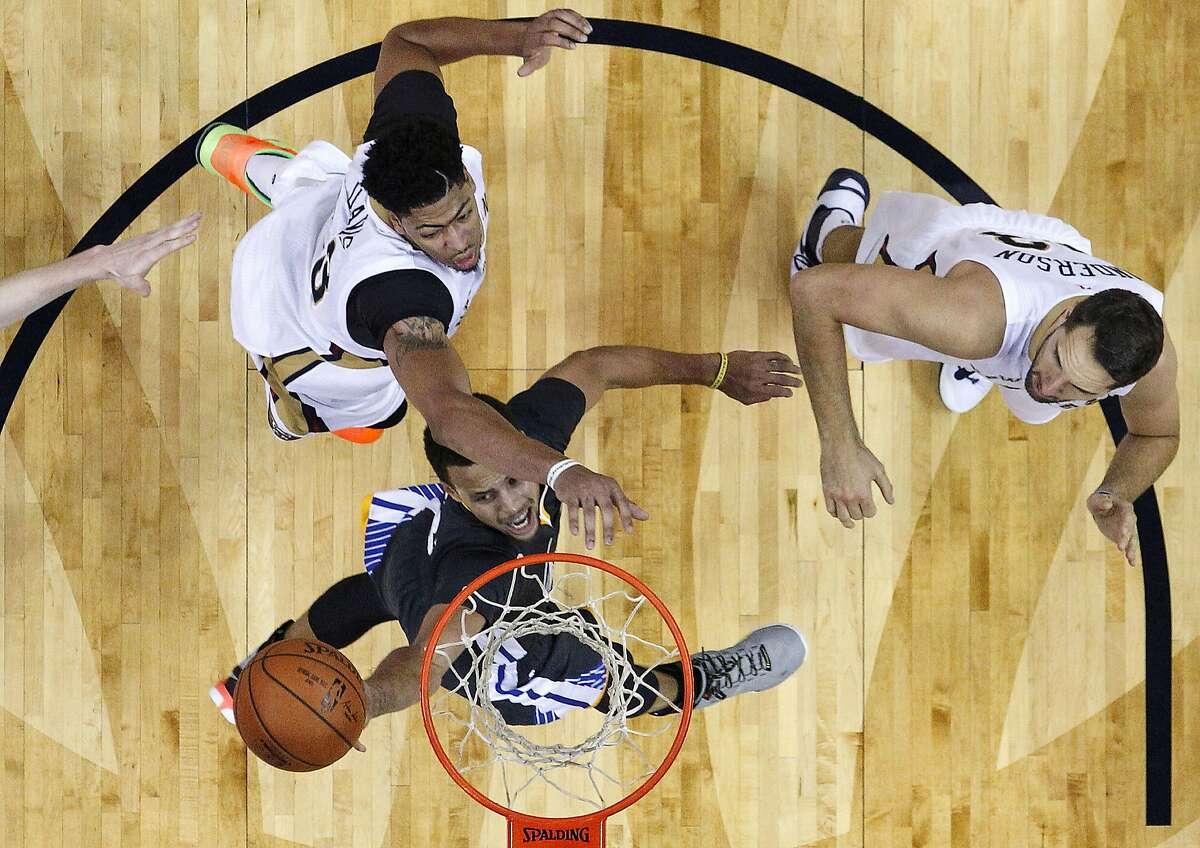 Golden State Warriors guard Stephen Curry (30) goes to the basket between New Orleans Pelicans forward Anthony Davis, left, and forward Ryan Anderson in the second half of an NBA basketball game in New Orleans, Saturday, Oct. 31, 2015. The Warriors won 134-120. (AP Photo/Gerald Herbert)
