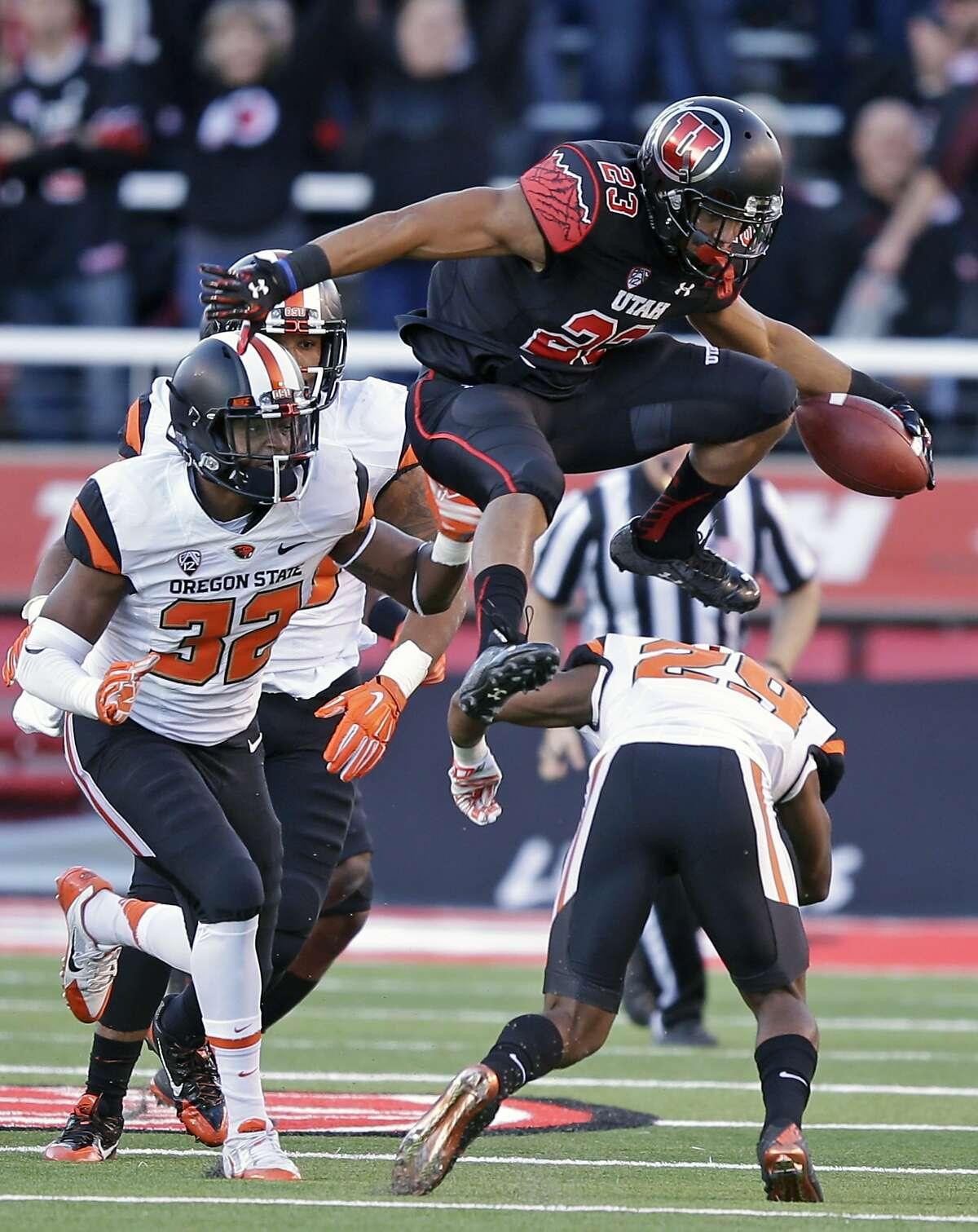 Utah running back Devontae Booker (23) leaps over Oregon State cornerback Dwayne Williams (29) as teammate linebacker Jonathan Willis (32) pursues in the first quarter of an NCAA college football game Saturday, Oct. 31, 2015, in Salt Lake City. (AP Photo/Rick Bowmer)