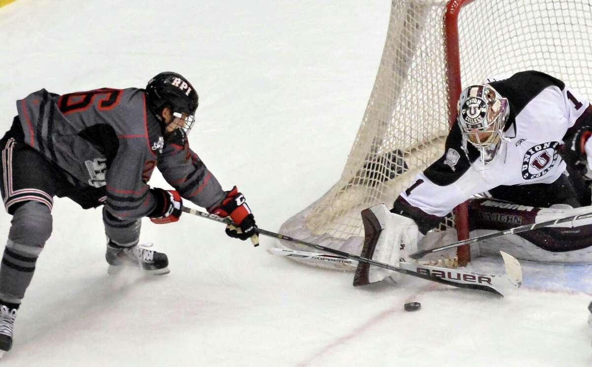 RPI's #26 Mark Miller, left, tries to get the puck around Union goalie Alex Sakellaropoulos during Saturday's game at the Houston Field House Oct. 31, 2015 in Troy, NY. (John Carl D'Annibale / Times Union)
