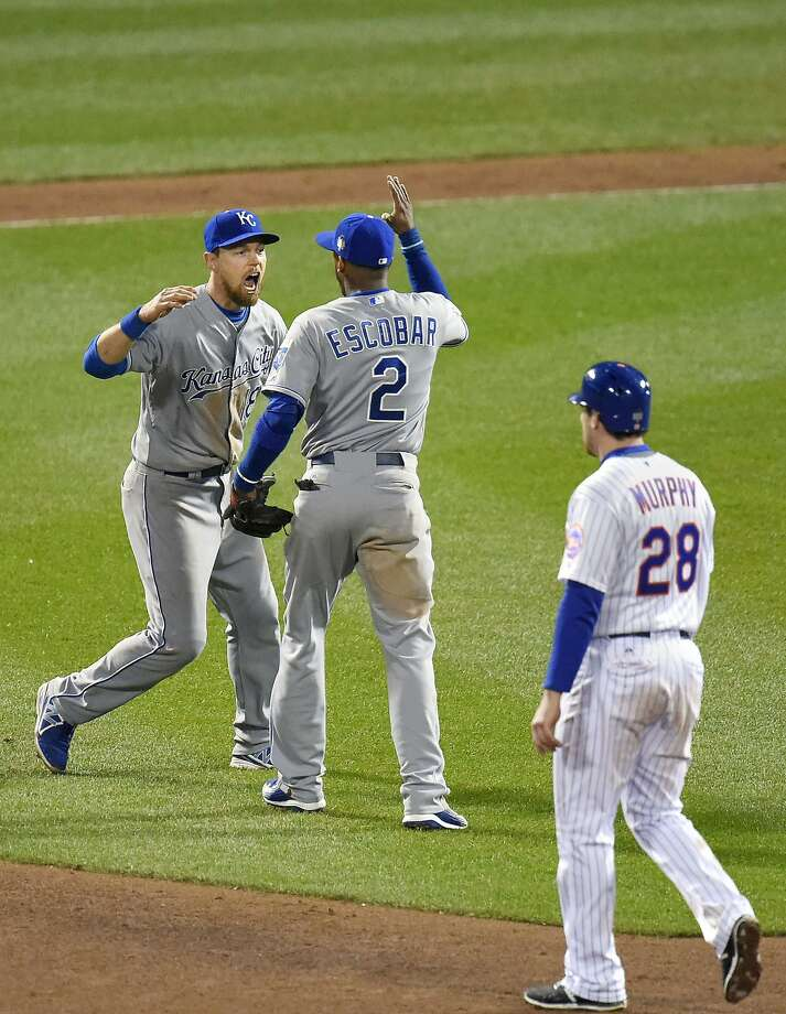 Kansas City Royals second baseman Ben Zobrist and shortstop Alcides Escobar (2) celebrate in front of the New York Mets' Daniel Murphy (28) after a 5-3 win for a 3-1 series lead Game 4 of the World Series on Saturday, Oct. 31, 2015, at Citi Field in New York. (David Eulitt/Kansas City Star/TNS) Photo: David Eulitt, McClatchy-Tribune News Service