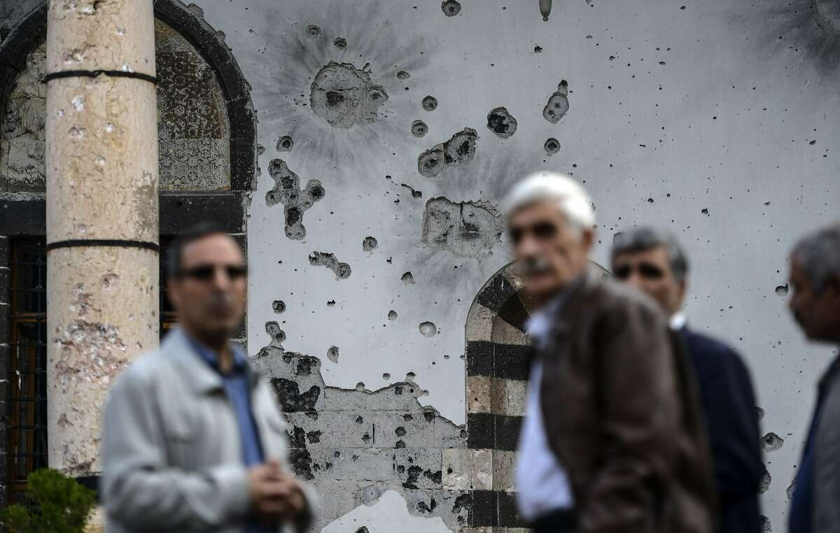 Men stand in front of a bullet-riddled wall that was damaged during clashes between Turkish troops and Kurdish militants in the district of Sur in Diyarbakir, southeastern Turkey, on October 31, 2015 on the eve of the country's general election. Turkish politicians rallied their supporters on the eve of a vote many fear is unlikely to bring an end to months of instability as the country confronts a bloody wave of jihadist attacks and a renewed Kurdish conflict.