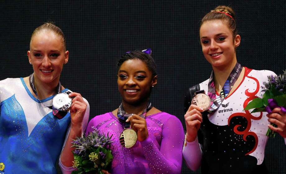 Gold medal winner Simone Biles of the U.S., center, silver medal winner Sanne Wevers of the Netherlands, left, and Bronze medal winner Germany's Pauline Schaefer pose on the podium after the balance beam exercise during the women's apparatus final competition at the World Artistic Gymnastics championships at the SSE Hydro Arena in Glasgow, Scotland, Sunday, Nov. 1, 2015. (AP Photo/Matthias Schrader) Photo: Matthias Schrader, Associated Press / AP