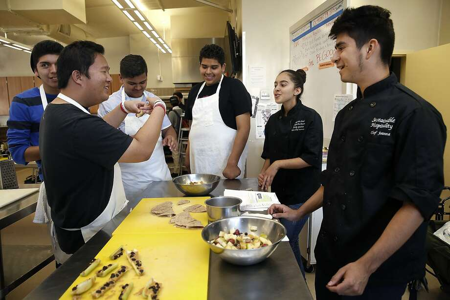 Cooking Matters instructors Celeste Rios and Daniel Hernandez (in black chef coats at right) talk food with the students at Mount Diablo High School in Concord. Photo: Liz Hafalia, The Chronicle