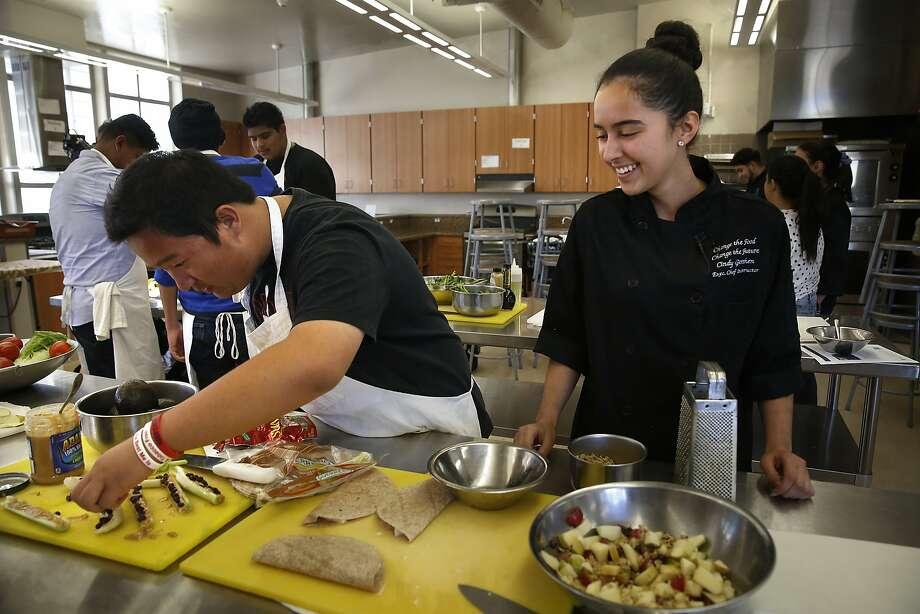 Mount Diablo High School junior Danny (left) makes celery log snacks with the supervision of Cooking Matters teacher Celeste Rios. Photo: Liz Hafalia, The Chronicle