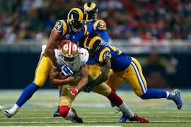 ST. LOUIS, MO - NOVEMBER 1: Colin Kaepernick #7 of the San Francisco 49ers is sacked by Robert Quinn #94 and James Laurinaitis #55 of the St. Louis Rams in the fourth quarter at the Edward Jones Dome on November 1, 2015 in St. Louis, Missouri. (Photo by Dilip Vishwanat/Getty Images)