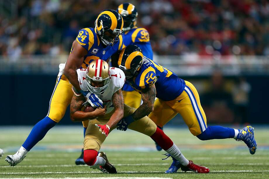 Colin Kaepernick of the San Francisco 49ers is sacked by Robert Quinn #94 and James Laurinaitis #55 of the St. Louis Rams in the fourth quarter at the Edward Jones Dome on November 1, 2015 in St. Louis, Missouri. Photo: Dilip Vishwanat, Getty Images