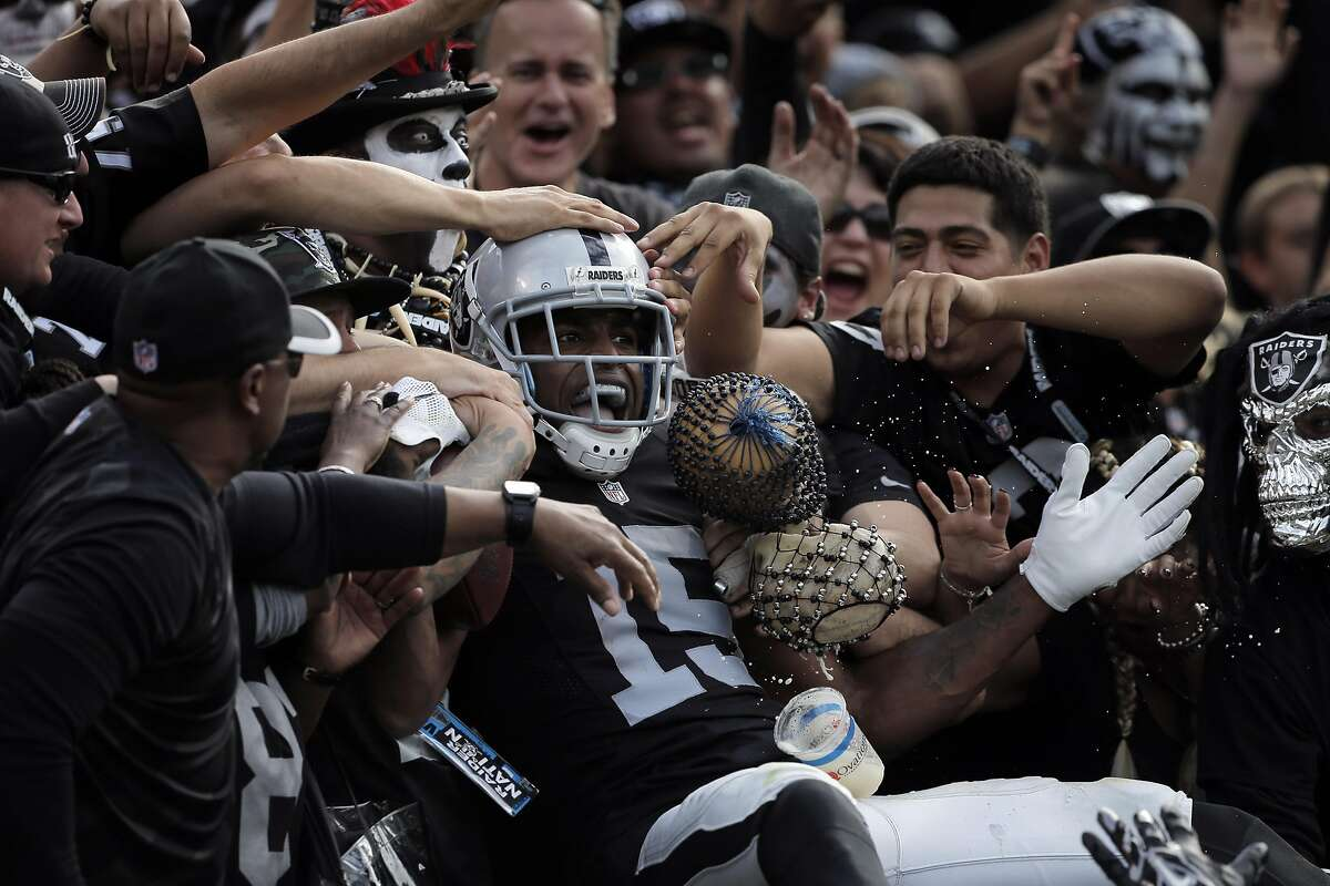 Michael Crabtree (15) gets swallowed up by The Black Hole after scoring a touchdown in the second quarter as the Oakland Raiders played the New York Jets at O.co Coliseum in Oakland, Calif., on Sunday, November 1, 2015.