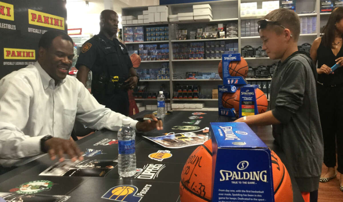 David Robinson signs a poster for a boy at Sports Cards Plus in San Antonio on Monday, Oct. 26, 2015. Robinson was in attendance to help the store celebrate a $75,000 makeover.