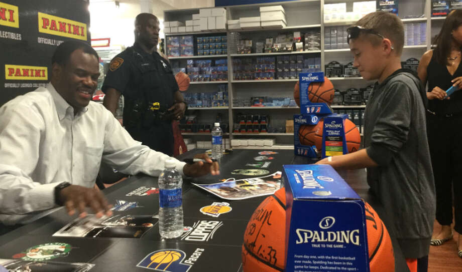 David Robinson signs a poster for a boy at Sports Cards Plus in San Antonio on Monday, Oct. 26, 2015. Robinson was in attendance to help the store celebrate a $75,000 makeover. Photo: Jabari Young / San Antonio Express-News