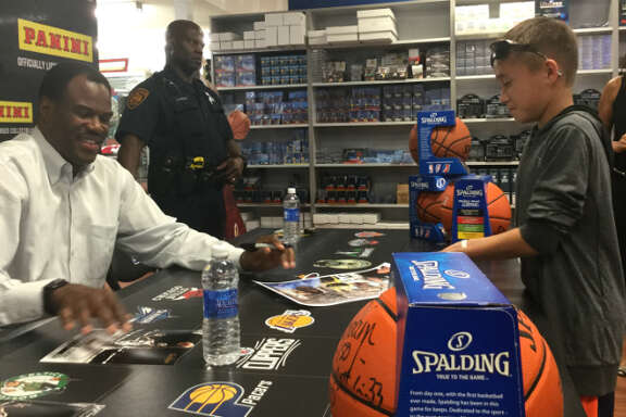 David Robinson signs a poster for a boy at Sports Cards Plus in San Antonio on Monday, Oct. 26, 2015. Robinson was in attendance to help the store celebrate a $75.000 makeover.
