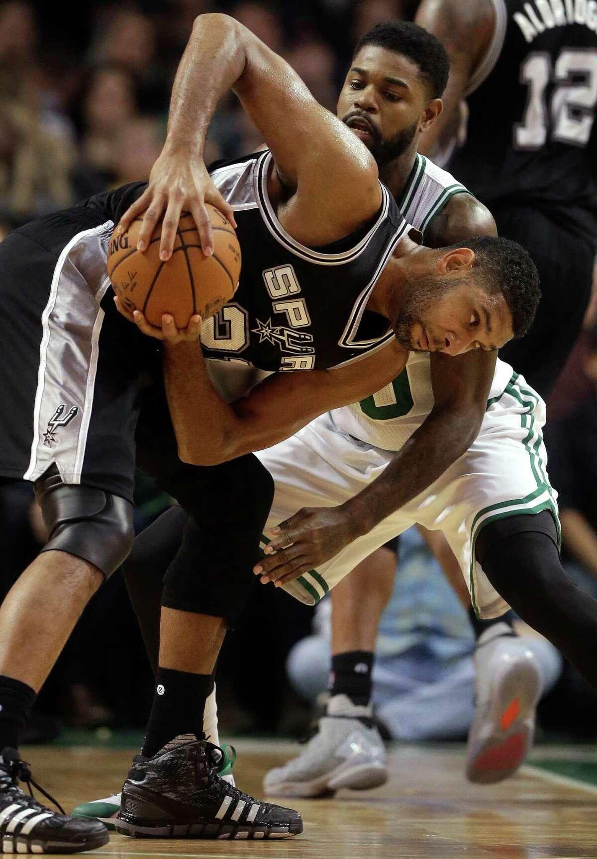 San Antonio Spurs forward Tim Duncan, front, tries to drive past Boston Celtics forward Amir Johnson, behind, in the third quarter of an NBA basketball game, Sunday, Nov. 1, 2015, in Boston. The Spurs won 95-87. (AP Photo/Steven Senne)