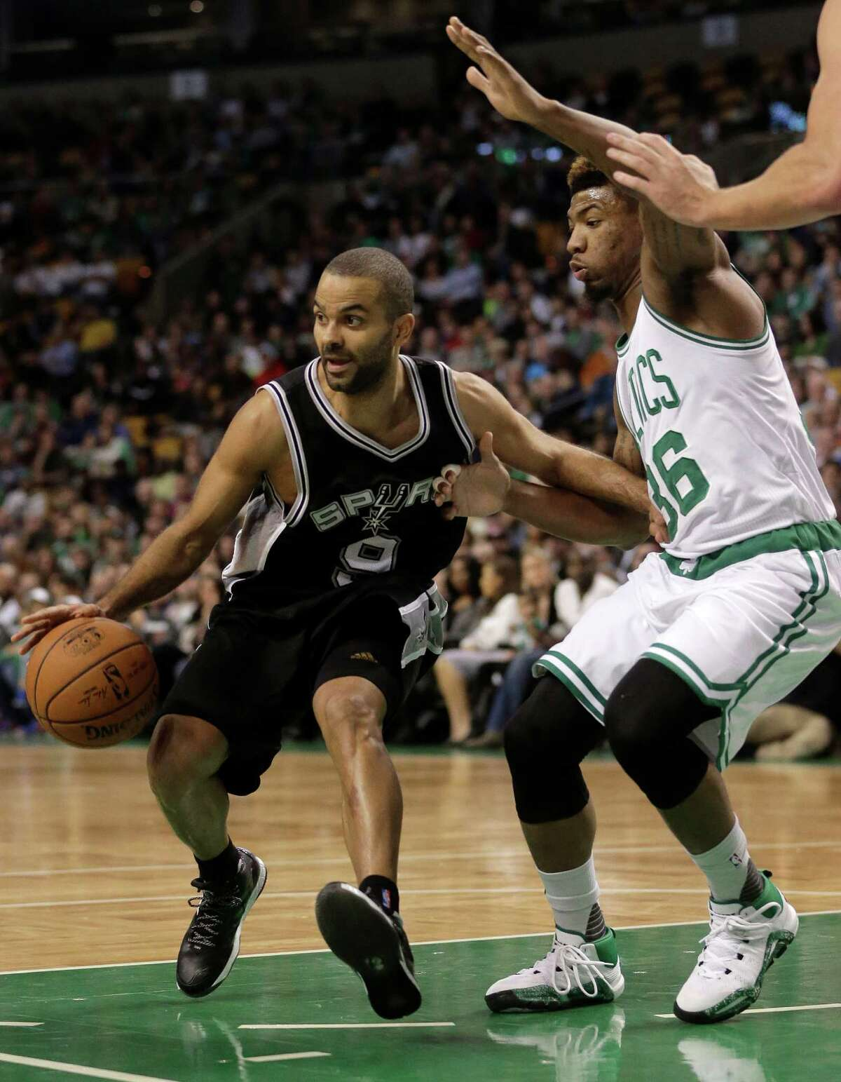 San Antonio Spurs guard Tony Parker, of France, left, drives toward the basket past Boston Celtics guard Marcus Smart, right, in the first quarter of an NBA basketball game, Sunday, Nov. 1, 2015, in Boston. (AP Photo/Steven Senne)