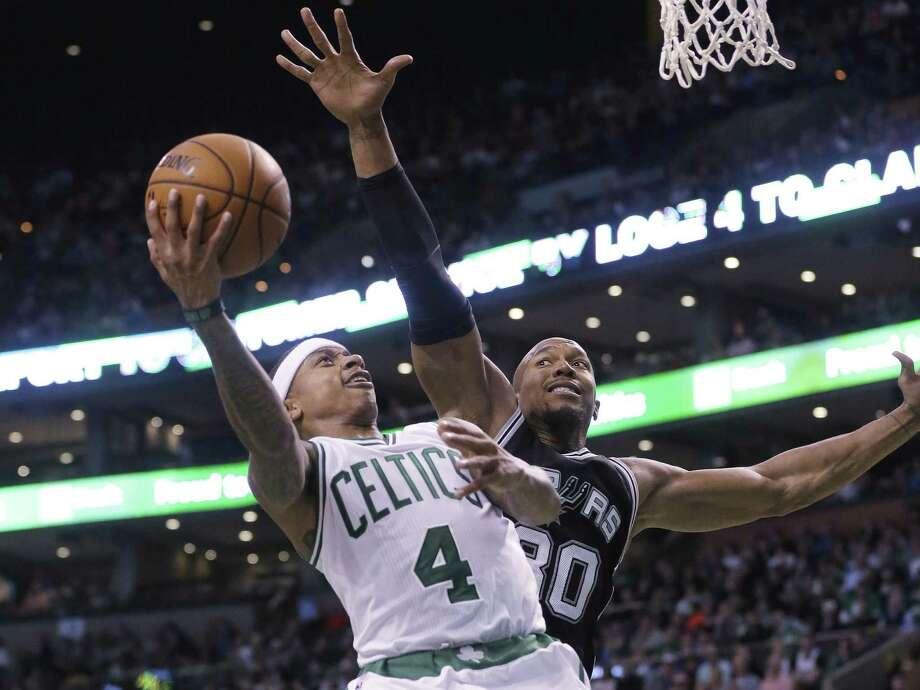 Boston Celtics guard Isaiah Thomas, left, takes a shot at the basket as San Antonio Spurs forward David West, right, tries to block him in the third quarter of an NBA basketball game, Sunday, Nov. 1, 2015, in Boston. The Spurs won 95-87. (AP Photo/Steven Senne) Photo: Steven Senne, STF / Associated Press / AP