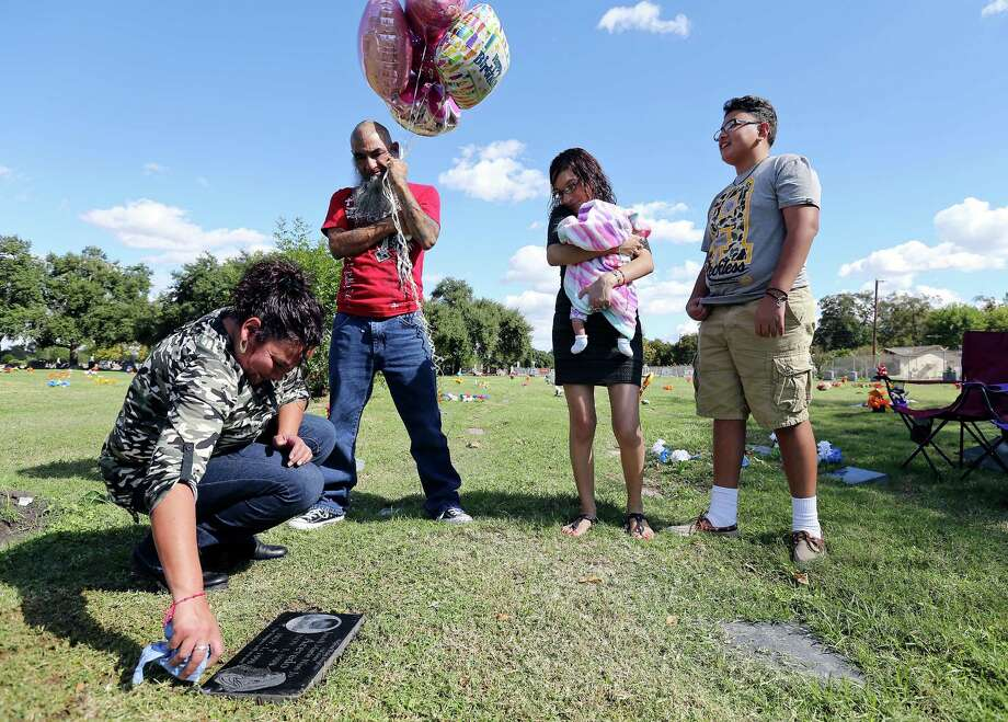 Yvonne Acevedo cleans the headstone on her daughter's Jenell Marie Neri Jo Acevedo's grave as her husband Jose (from left) and children Desirae, and Jayden look on Sunday Nov. 1, 2015 at San Fernando Cemetery II. Photo: Edward A. Ornelas, Staff / San Antonio Express-News / © 2015 San Antonio Express-News