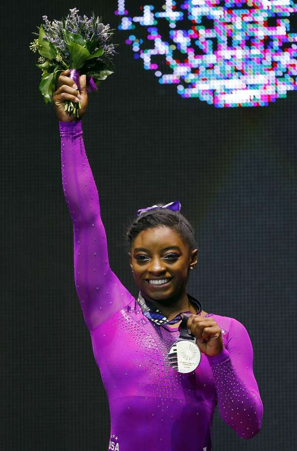 Gold medal winner Simone Biles of the U.S. pose on the podium after the balance beam exercise during the women's apparatus final competition at the World Artistic Gymnastics championships at the SSE Hydro Arena in Glasgow, Scotland, Sunday, Nov. 1, 2015. (AP Photo/Matthias Schrader) Photo: Matthias Schrader, Associated Press