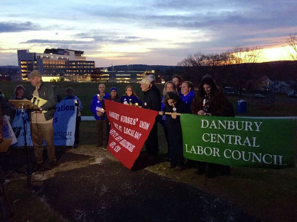 Participants brought banners to the vigil supporting health care workers at Danbury and New Milford hospitals. Danbury Hospital is visible in the background.
