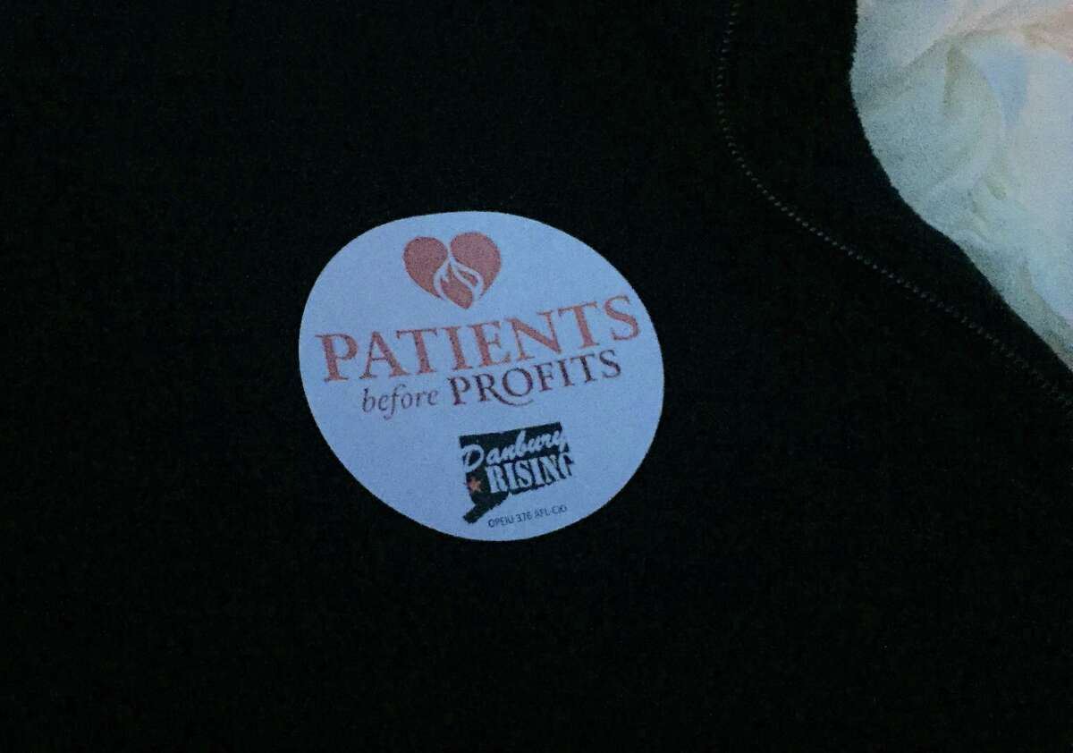 Many in attendance at the vigil supporting health care workers at Danbury and New Milford hospitals wore stickers with the slogan,