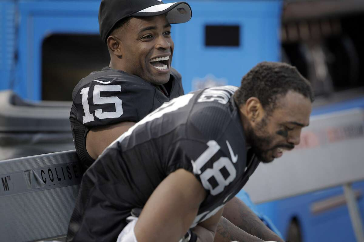Michael Crabtree (15) and Andre Holmes (18) laugh on the bench in the final moments of the fourth quarter as the Oakland Raiders played the New York Jets at O.co Coliseum in Oakland, Calif., on Sunday, November 1, 2015.