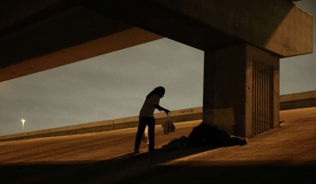 Covenant House's Jaren Bernard delivers meals under an overpass on Friday as part of an outreach to find Houston's homeless young adults.
