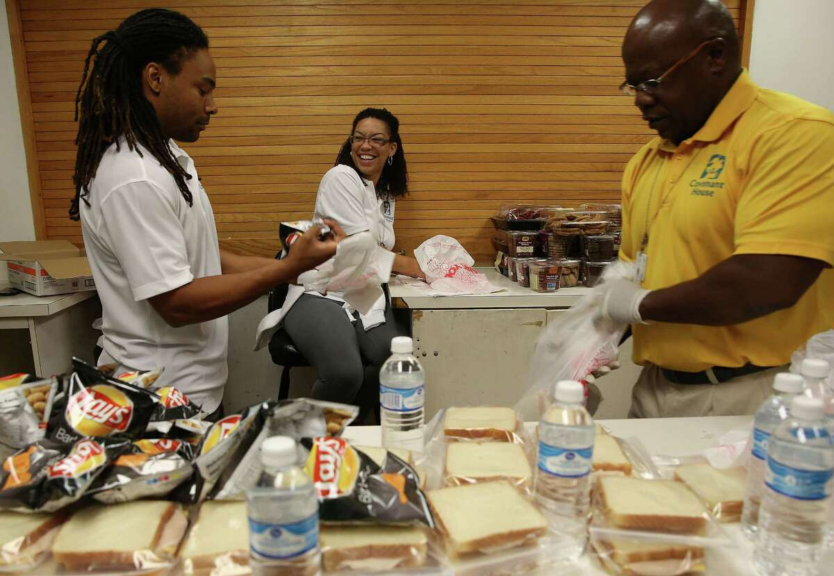Jaren Bernard, left, Chrystal Lovings-Bernard and Mike Blockson prepare sandwiches to pass out to homeless youth.