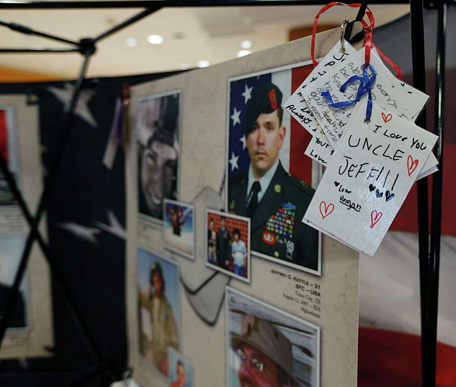 Collected notes to the departed that family and friends leave are laminated and attached to photos in the Remembering our Fallen traveling memorial. Photo: James Nielsen, Staff / © 2015  Houston Chronicle