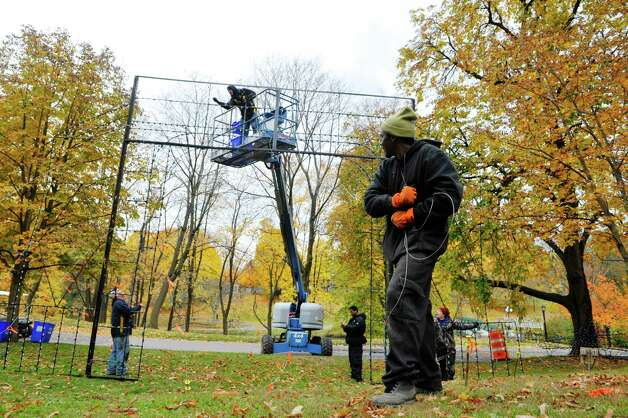 Police Athletic League volunteers, from left to right, Nathan Czamara, his brother, David Czamara, Uzziah Fantroy, Michael Scales and Nick Brockley work to set up  more than 125 illuminated displays and scenes for the 19th Annual Price Chopper Capital Holiday Lights on Sunday, Nov. 1, 2015, in Washington Park in Albany, N.Y.  The lights display opens to the public on November 27.    (Paul Buckowski / Times Union) Photo: PAUL BUCKOWSKI / 00034006A