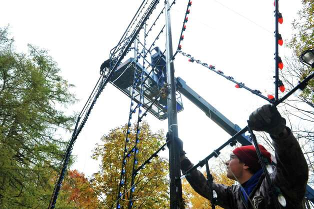 Police Athletic League volunteers David Czamara, left, and Nick Brockley install a light display with other volunteers as they worked to set up  more than 125 illuminated displays and scenes for the 19th Annual Price Chopper Capital Holiday Lights on Sunday, Nov. 1, 2015, in Washington Park in Albany, N.Y.  The lights display opens to the public on November 27th.    (Paul Buckowski / Times Union) Photo: PAUL BUCKOWSKI / 00034006A