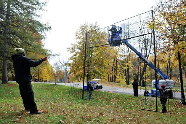 Police Athletic League volunteers, from left to right, Michael Scales, Nathan Czamara, David Czamara, Uzziah Fantroy and Nick Brockley install one of the large light displays as they worked to set up  more than 125 illuminated displays and scenes for the 19th Annual Price Chopper Capital Holiday Lights on Sunday, Nov. 1, 2015, in Washington Park in Albany, N.Y.  The lights display opens to the public on November 27.    (Paul Buckowski / Times Union) Photo: PAUL BUCKOWSKI / 00034006A