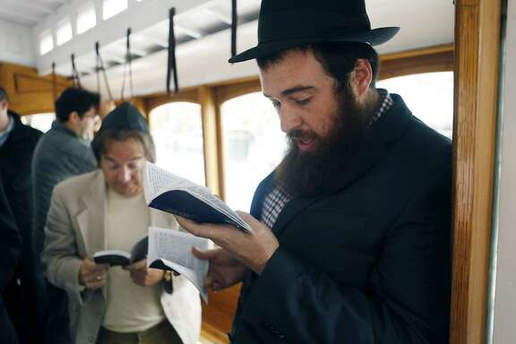 Rabbi Moshe Langer, right, leads prayers on the Mitzvah Cable Car in downtown San Francisco.