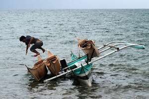 TOPSHOTS A boatman (L) jumps from his motorised boat after it tilted due to waves while unloading newly-made wooden fishing boats at the coastal village of San Jose in Tacloban City, Leyte province, central Philippines on November 1, 2015, a week before the second anniversary of the devastating typhoon on November 8. The Philippines has not done enough to rebuild after Super Typhoon Haiyan, as thousands remain in shanties without power or water for nearly two years, a United Nations representative said in August.    AFP PHOTO / TED ALJIBETED ALJIBE/AFP/Getty Images