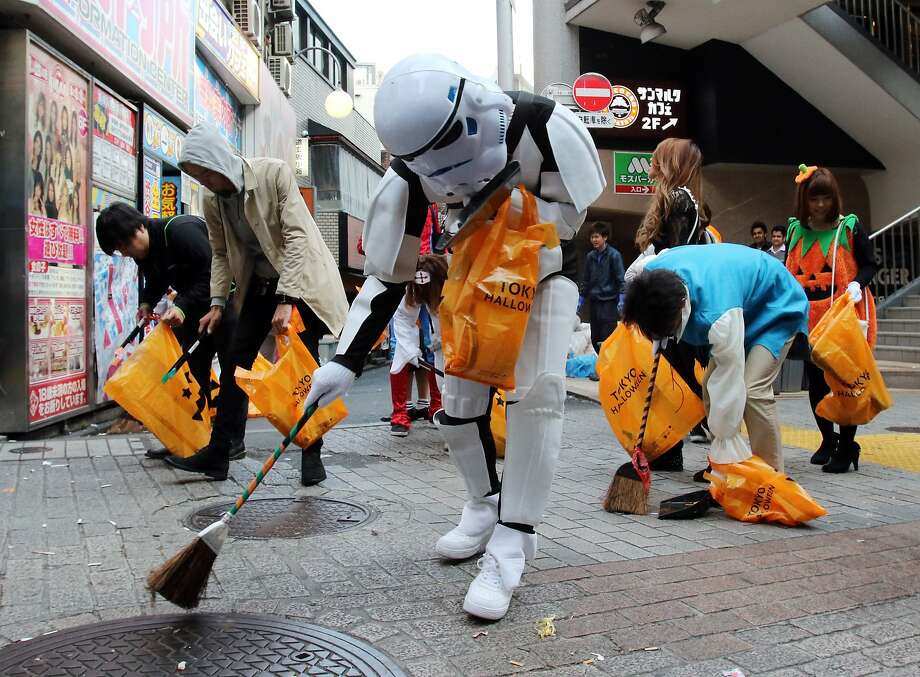 People in costumes collect garbage on the street after their Halloween party at Tokyo's Shibuya fashion district on November 1, 2015.  Hundreds of volunteers collected garbage to make an art object for the Tokyo Design Week art event. Photo: Yoshikazu Tsuno, AFP / Getty Images