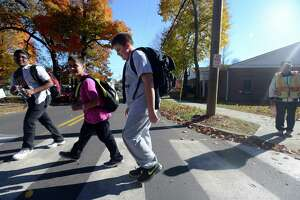 Harborside Middle School students Abhiram Pulicherla, John Belbusti and Alex Byron, from left, cross the intersection at High Street and Jepson Drive in Milford Friday, Oct. 30, 2015. The district is considering a plan to shorten walking distances for middle and high school students.