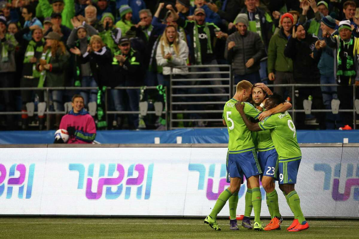 Seattle's Andy Rose (left), Andreas Ivanschitz (center) and Obafemi Martins (right) celebrate Ivanschitz's goal in the second half of game one of the MLS Conference Semifinals, Sunday, Nov. 1, 2015 at CenturyLink Field. The Sounders won 2-1.
