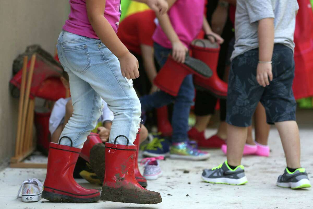 Students at Pre-K for SA North Education Center put on boots to go play in the mud area on Tuesday, Oct. 6, 2015. They get to spend outside time enjoying a variety of activity centers.