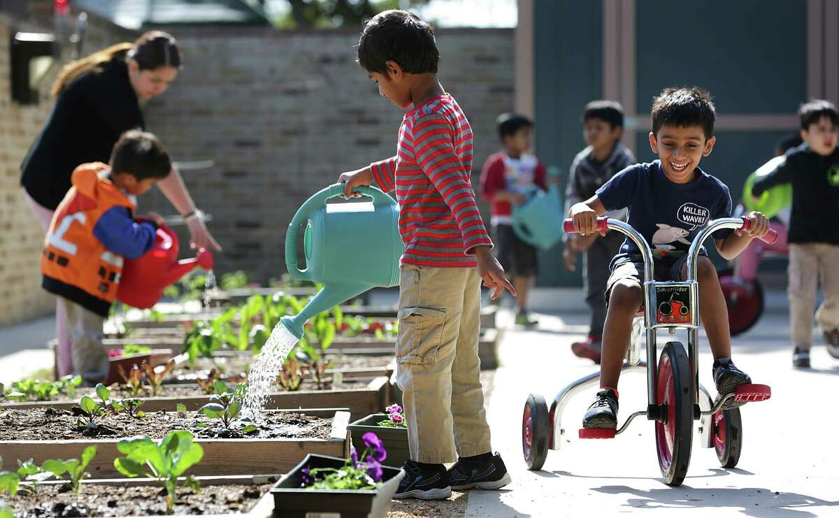 Rushil Muthyala (right) zips by on a tricycle past Sri Vibhav, who's watering plants in the garden at Pre-K for SA North Education Center.
