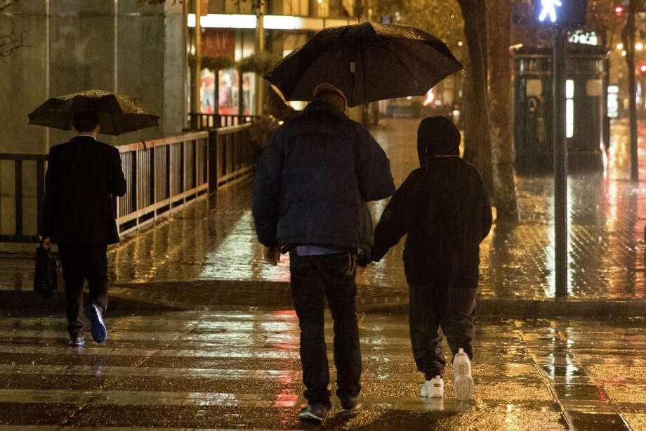 Pedestrians walk through the rain in San Francisco early Monday morning November 2, 2015. Photo: SF Gate / Douglas Zimmerman