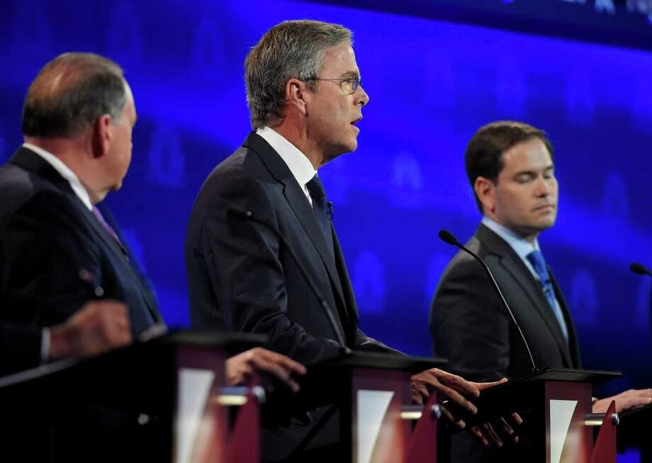 Jeb Bush, center, flanked by Mike Huckabee, left, and Marco Rubio responds to a question during the CNBC Republican presidential debate at the University of Colorado, last week. Photo: Mark J. Terrill /Associated Press / AP