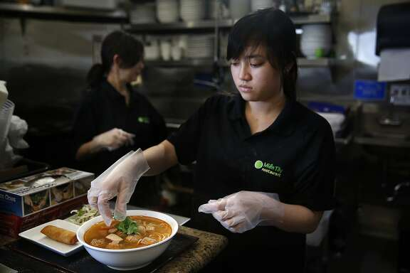 Helper My Tren places cilantro on Bun rieu cau--vermicelli, w/crab and tomato broth, topped w/fried tofu, mushroom, crab, shrimp and pork meat balls served with green onion, and fresh garnishes--prepared at Mien Tay in Oakland, Calif., on Friday, October 30, 2015.
