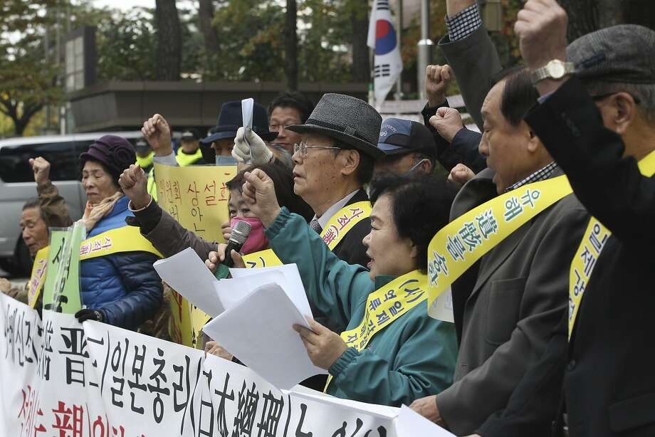 South Koreans protest Japanese Prime Minister Shinzo Abe's visit to Seoul at the Japanese Embassy. Many South Koreans believe Abe has tried to whitewash Japan's wartime atrocities. Photo: Ahn Young-joon, Associated Press