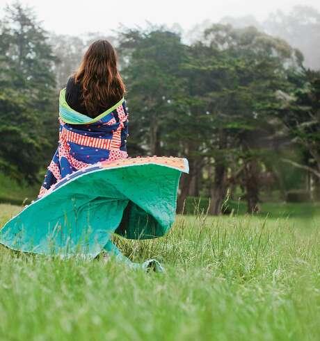"A woman wraps herself in Sherri Lynn Wood's ""Rhythmic Grid"" quilt. Photo: Sara Remington"