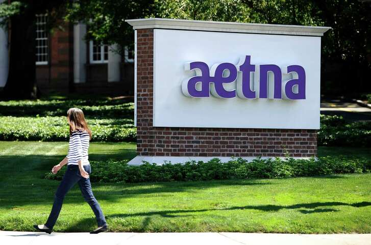 FILE - In this Tuesday, Aug. 19, 2014 file photo, pedestrian walks past a sign for health insurer Aetna Inc., at the company headquarters in Hartford, Conn.  Aetna Inc. and General Electric Co. are threatening to leave Connecticut, claiming tax increases in the new state budget were unfriendly to business.  In response , legislators have created a commission to study the state's economic competitiveness.  (AP Photo/Jessica Hill, File)