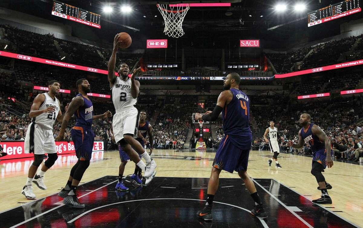 Spurs' Kawhi Leonard (2) attempts a shot between Phoenix Suns' Markieff Morris (11) and Tyson Chandler (4) during their preseason game at the AT&T Center on Oct. 20, 2015.