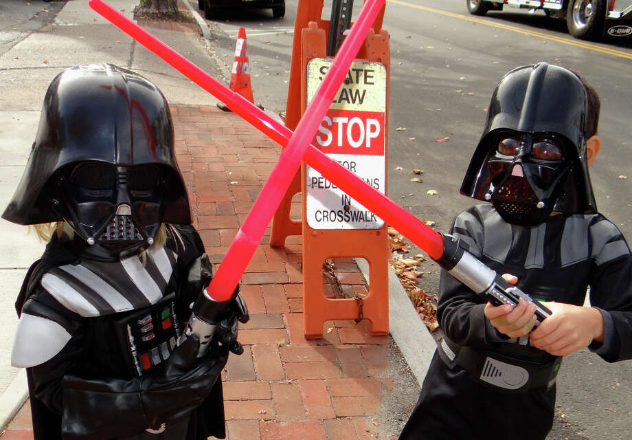 Grey Shugrue, 4, of Southport, and Henry Tolins-Cary, 5, of Fairfield, both dressed as Darth Vader, cross light sabres as the Halloween parade is about to begin Saturday in Southport Village. Photo: Mike Lauterborn / For Hearst Connecticut Media / Fairfield Citizen