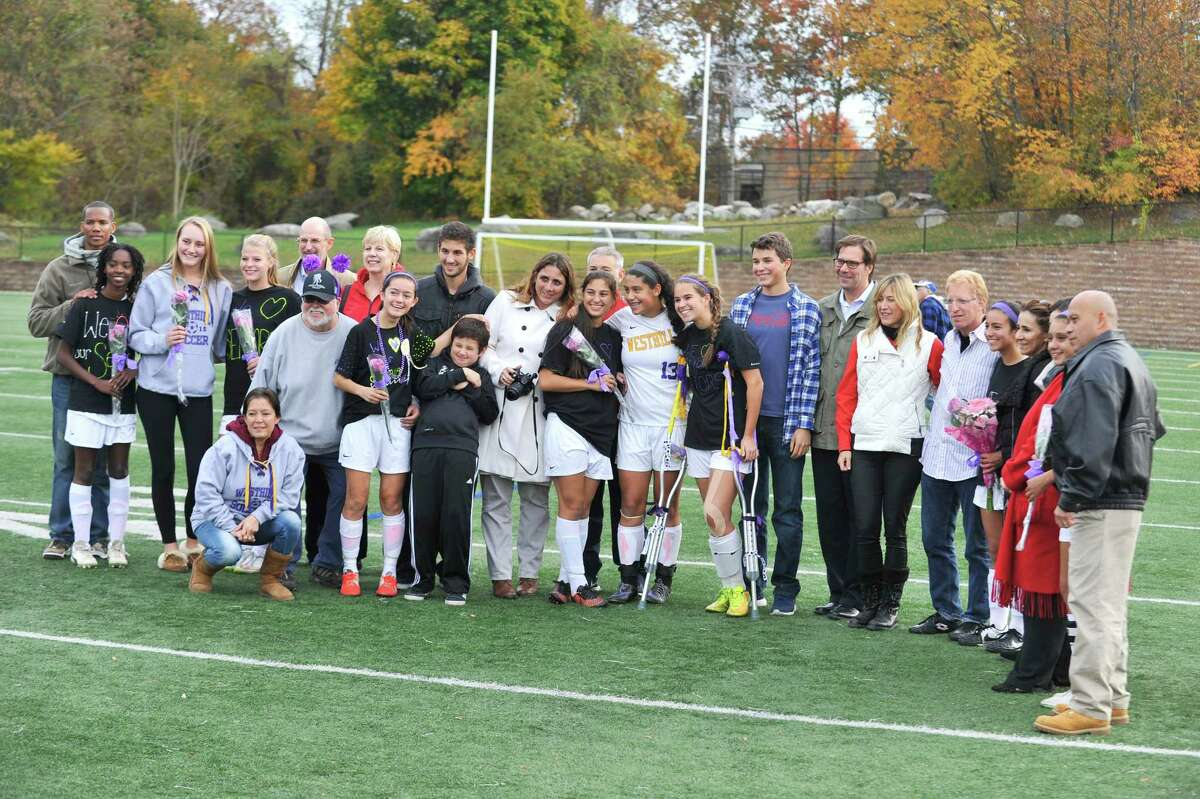 On Westhill High School's Varsity Soccer Senior Day, seven seniors are photographed with their families before the last home game of the season against Bridgeport Central. The Vikings won the game.