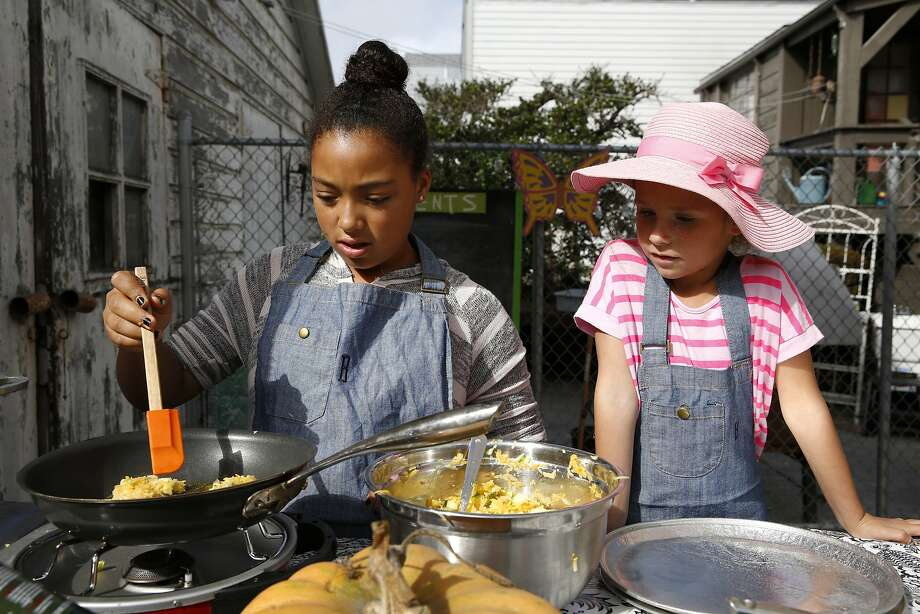 At Bay Leaf Kitchen in S.F., Junior Chef helper Sage (left) cooks fritters as Ava, 5, watches during class. Photo: Connor Radnovich, The Chronicle