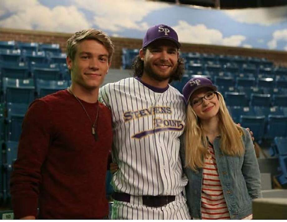 Giants shortstop Brandon Crawford poses with actors Dove Cameron (right) and Lucas Adams on a set at the Walt Disney Studios in Los Angeles.