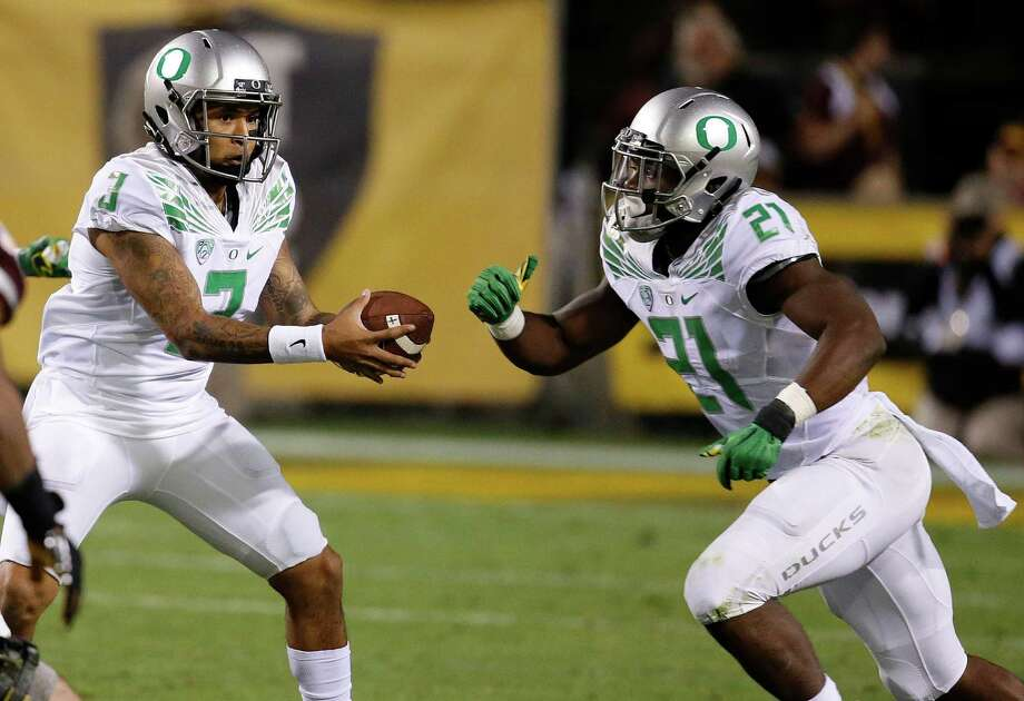 Oregon's Vernon Adams Jr. (3) fakes a handoff to Royce Freeman (21) during the first half of an NCAA college football game against Arizona State Thursday, Oct. 29, 2015, in Tempe, Ariz. (AP Photo/Ross D. Franklin) Photo: Ross D. Franklin / Associated Press / AP